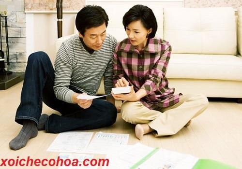 Hình ảnh hai vợ chồng bàn bạc xem ngày động thổ theo tuổi đàn ông.